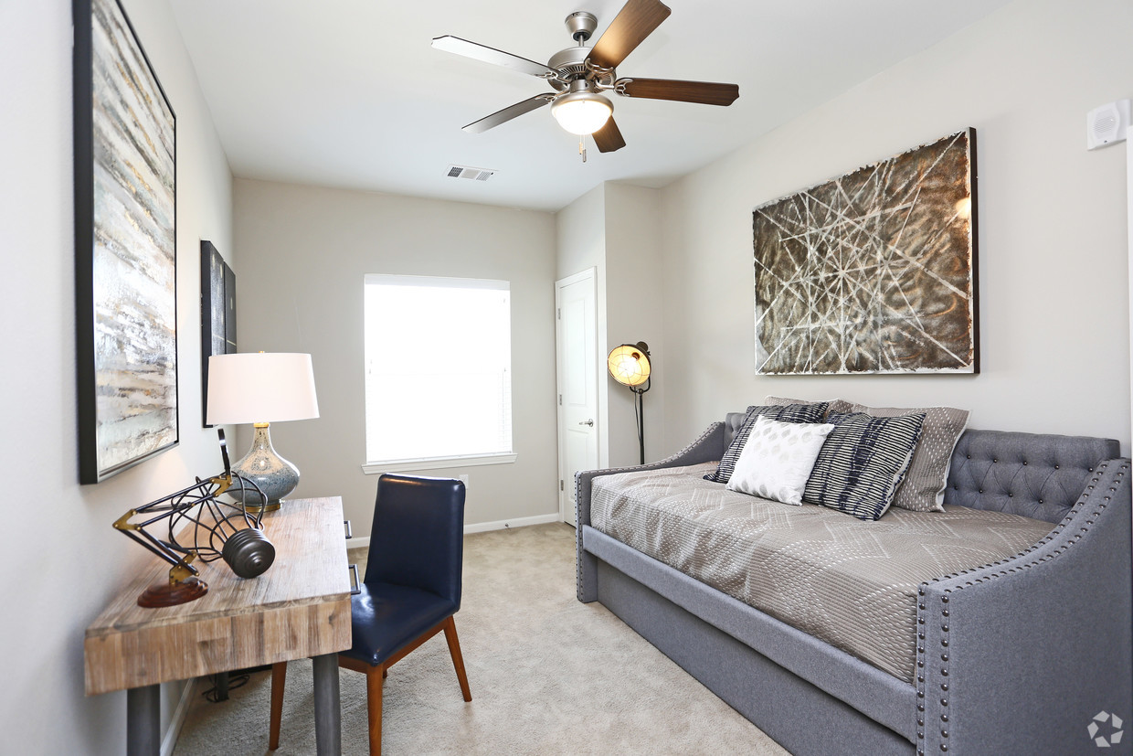 Bedroom at The Villages at Fiskville with grey day bed and table