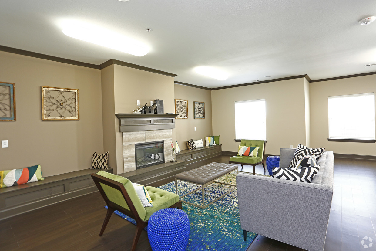The Villages at Fiskville community center with fireplace, grey couch, and green accent chairs