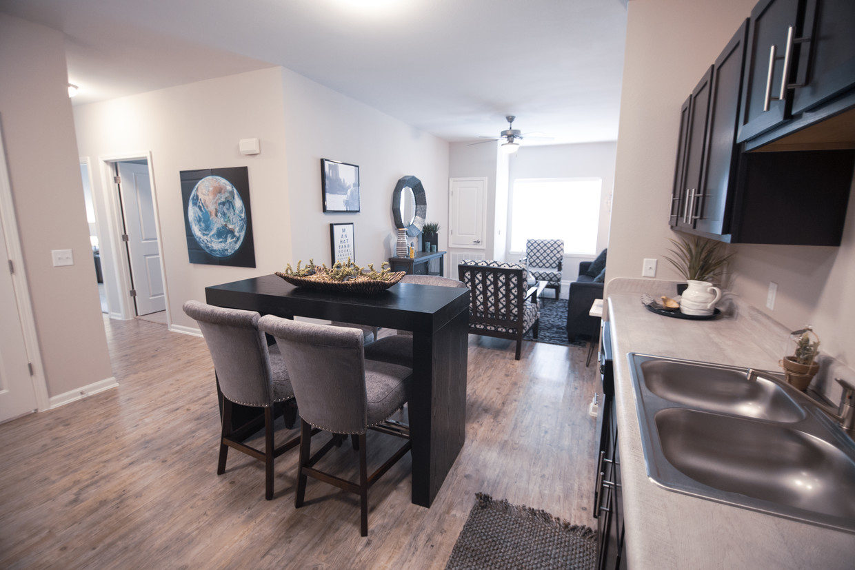 Villages at Fiskville kitchen with wood-look flooring, dark cabinets with a high-top table in the middle