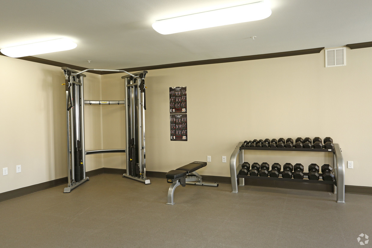 Villages at Fiskville fitness center with a rack of free weights and a weighted cable machine