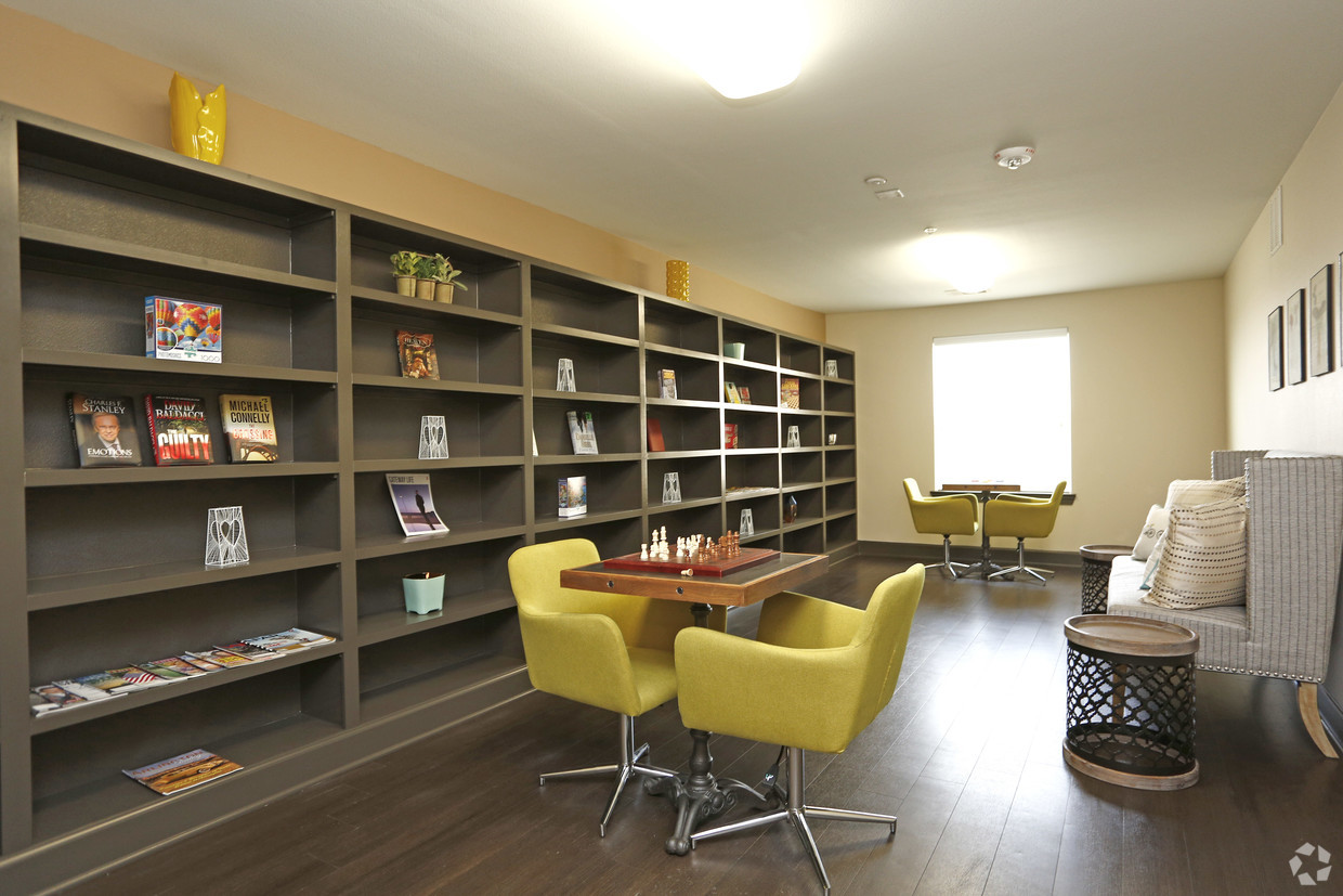 Villages at Fiskville Library with a complete wall of books and multiple sitting areas.
